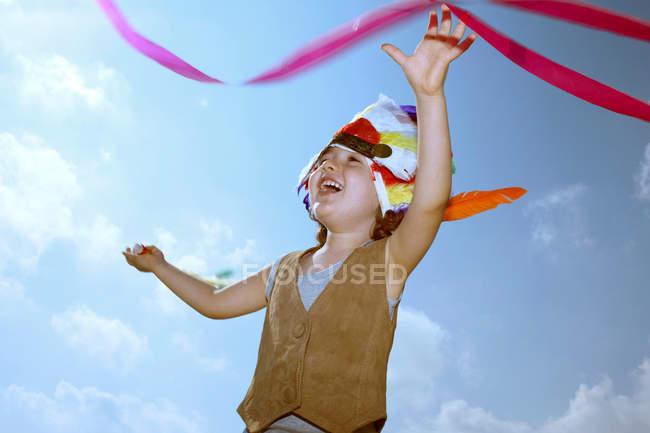 Niño en tocado indio con cinta contra el cielo azul - foto de stock