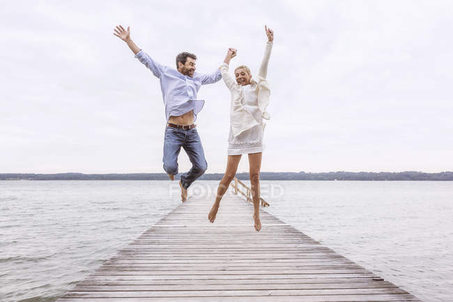 Mature couple jumping for joy on pier — Stock Photo