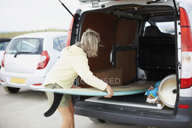 Senior woman putting surfboard in open van — Stock Photo