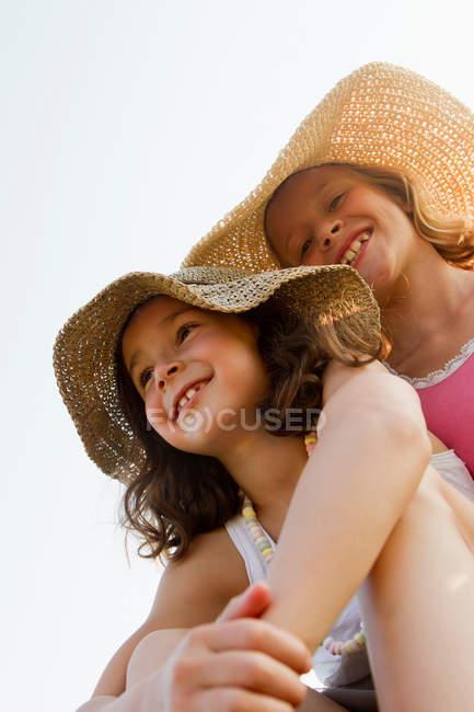 Lächelnde Mädchen mit Sonnenhüten im Freien — Stockfoto