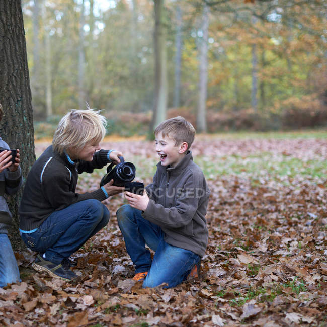 Boys pouring hot drink from flask in forest — Stock Photo
