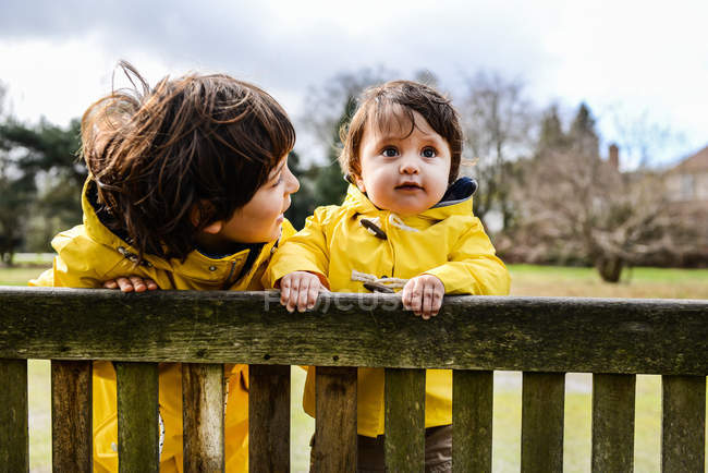 Portrait of baby boy and big brother in yellow anoraks on park bench — стокове фото