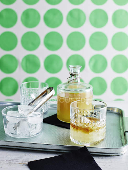 Decanter of lemon alcohol drink and glasses with ice on tray — Stock Photo