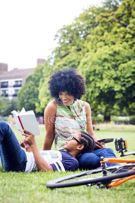 Junge und Mutter relaxen und lesen im Park — Stockfoto