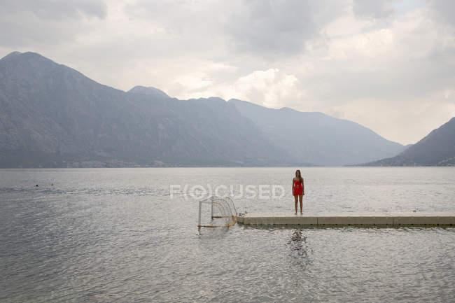 Mujer joven y solitaria de pie en el muelle, Bajova Kula, Montenegro - foto de stock