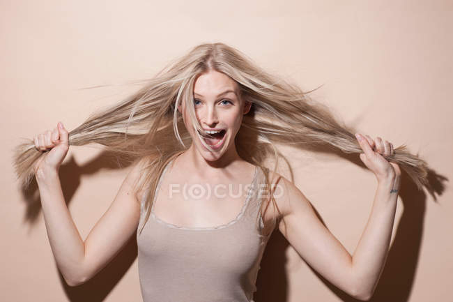 Portrait of young blonde woman holding hair and screaming — Stock Photo