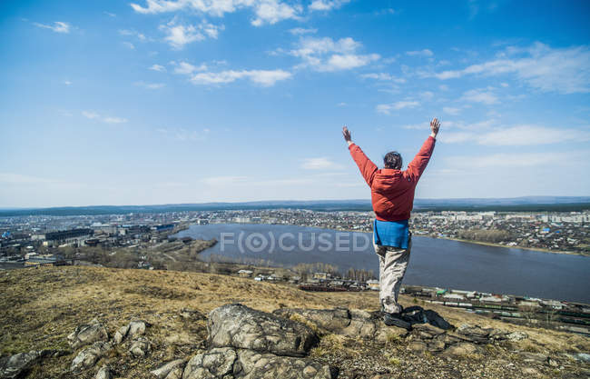 Rear view of young female hiker celebrating on top of mountains — Stock Photo