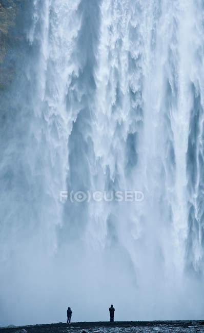 Silhueta dos caminhantes de encontro à cachoeira — Fotografia de Stock