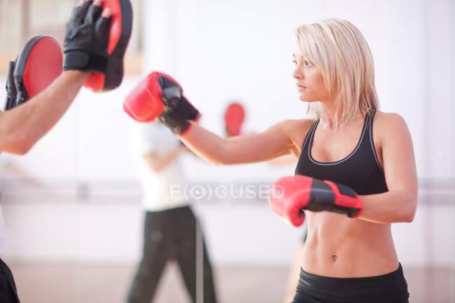 Jeune femme et entraîneur de boxe dans la salle de gym — Photo de stock