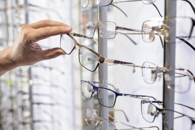 Customer choosing frames at small optics, close up — Stock Photo