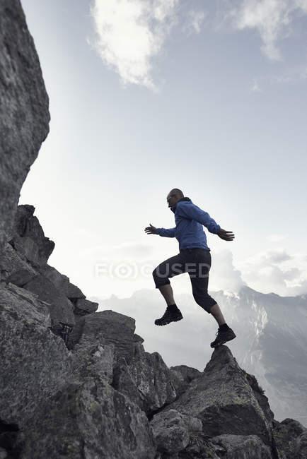 Hombre maduro saltando sobre rocas, Valais, Suiza - foto de stock