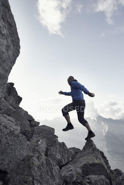 Mature man jumping on rocks, Valais, Switzerland — Stock Photo