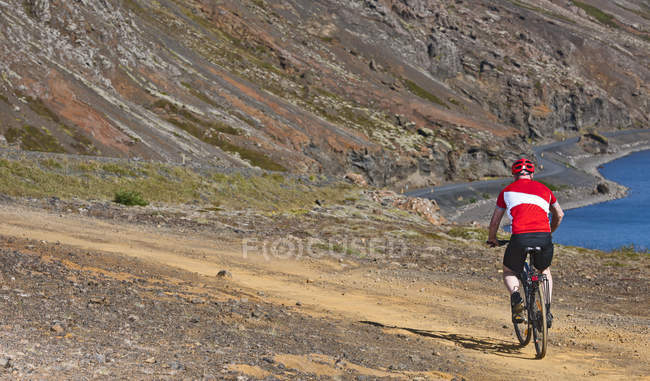 Cyclist cycling down track towards Kleifarvatn, Reykjanes, South West Iceland — Stock Photo