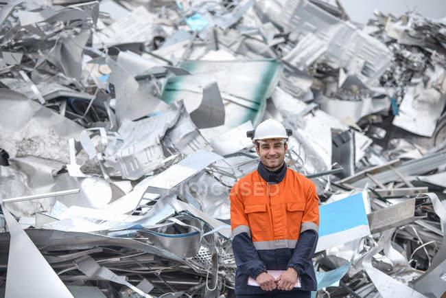 Портрет рабочего, стоящего перед металлоломом на заводе по переработке алюминия — стоковое фото