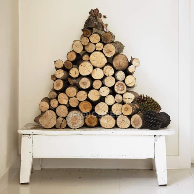 Pile de bois de chauffage sur banc — Photo de stock