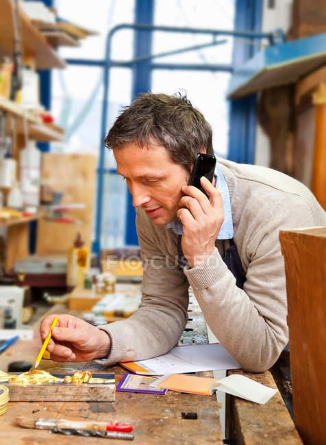 Карпентер Говорячи по телефону в магазині — стокове фото