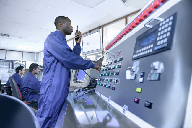 Workers in control room of car factory, one worker using walkie talkie at control panel — Foto stock