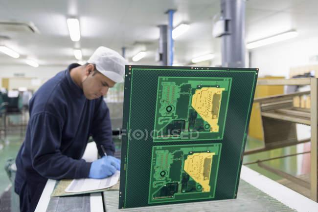Trabajador creando máquina de impresión de placa de circuito en fábrica de placa de circuito - foto de stock