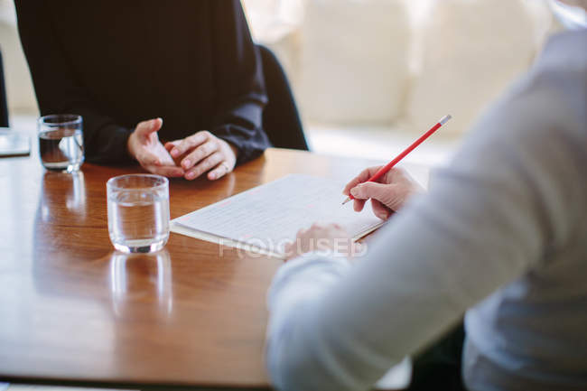 Cropped shot of mature businesswoman interviewing candidate at boardroom table — Stock Photo