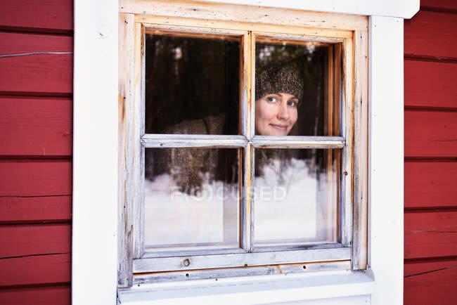 Porträt der jungen Frau peering aus Kabine Fenster, Posio, Lappland, Finnland — Stockfoto