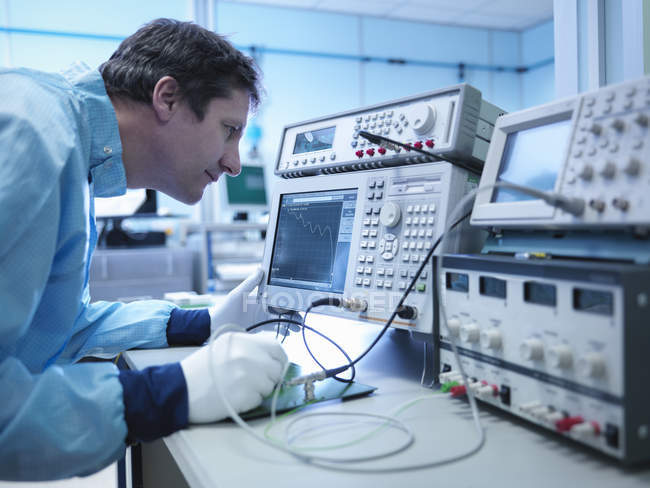 Electronics worker checking components in clean room — Stock Photo