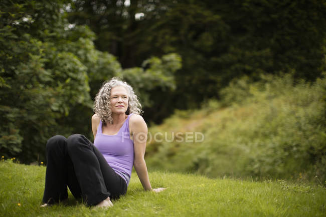 Mature woman taking a break from yoga practice in field — Stock Photo