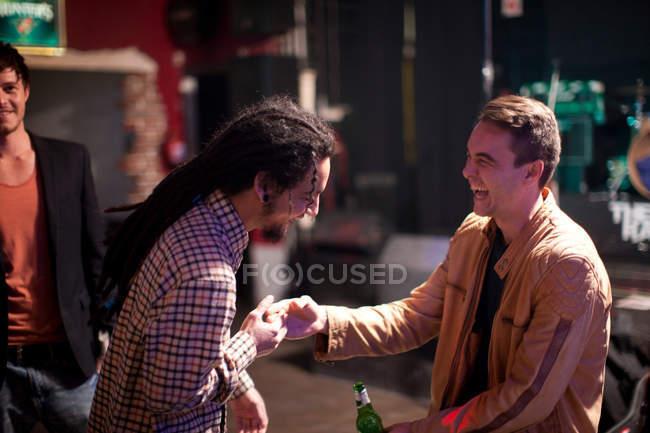 Улыбающиеся люди приветствие в бар — стоковое фото