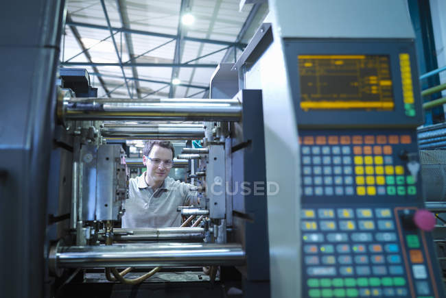 Worker with plastic injection moulding machine in plastics factory — Stock Photo