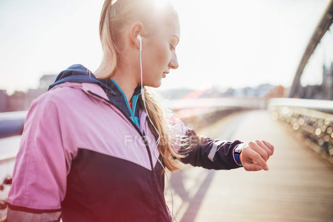 Mid adult female runner checking time on footbridge — Stock Photo