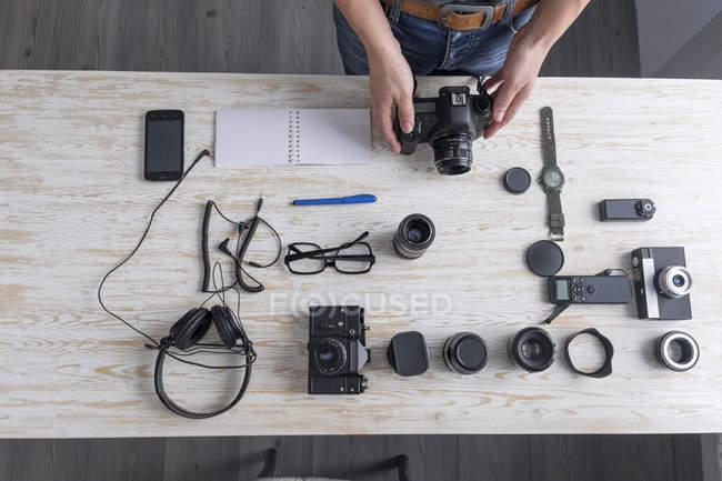 Обзор фотографа-мужчины, готовящего камеру на студийном столе — стоковое фото