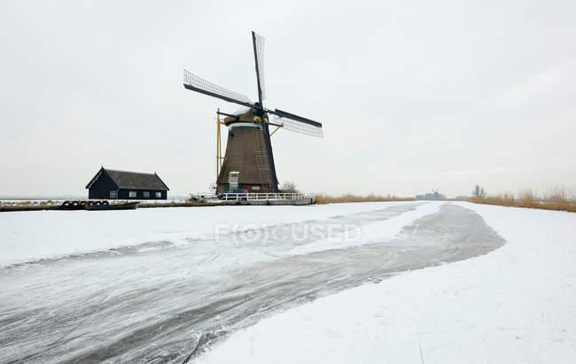 Molino de viento en paisaje nevado - foto de stock