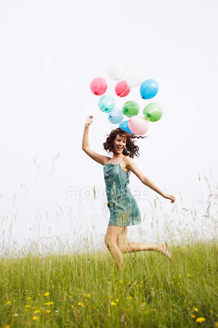 Woman with air balloons jumping in the field — Stock Photo