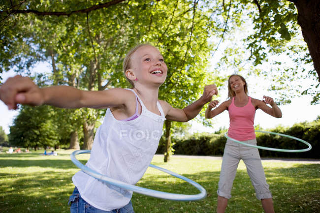 Mother and daughter with hula hoops — Stock Photo