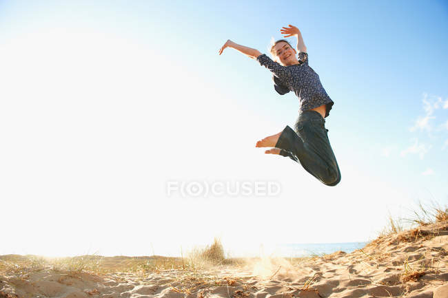 Smiling teenage girl jumping on beach — Foto stock