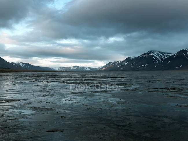 Flooded valley and snowcapped rocks under cloudy sky — Stock Photo