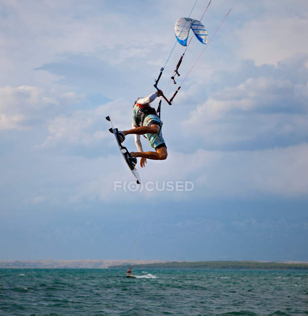 Kitesurfer jumping in the air and making trick — Stock Photo