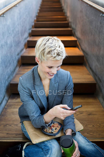 Woman using cell phone on lunch break — Stock Photo