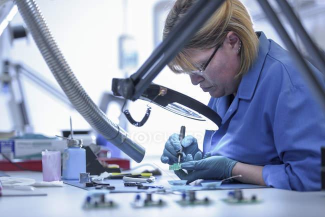 Arbeiterin montiert Elektronik in Elektronikfabrik — Stockfoto