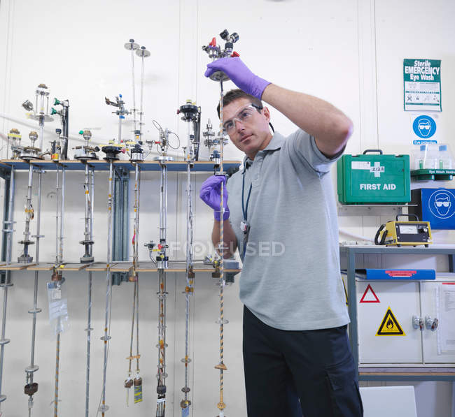Male scientist inspects particle accelerator target probes — Stock Photo
