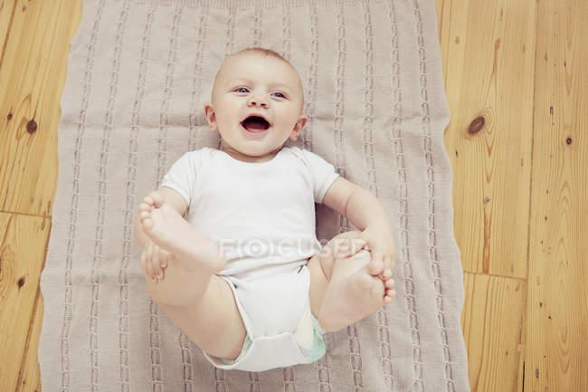 Портрет посміхаючись хлопчика, лежачи на ковдру — стокове фото