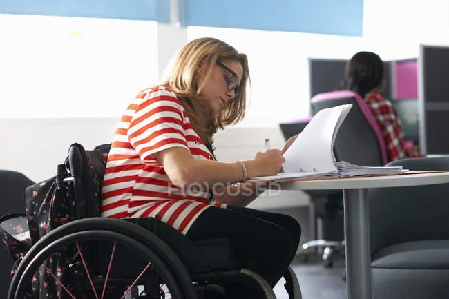 Ragazza adolescente in sedia a rotelle scrivere appunti in classe — Foto stock