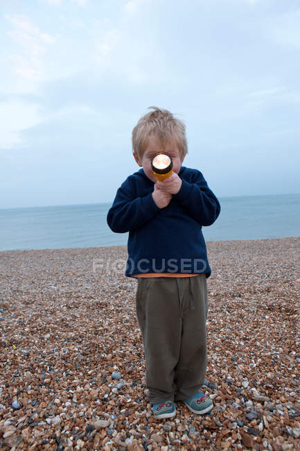 Boy with torch on pebble beach — Stock Photo