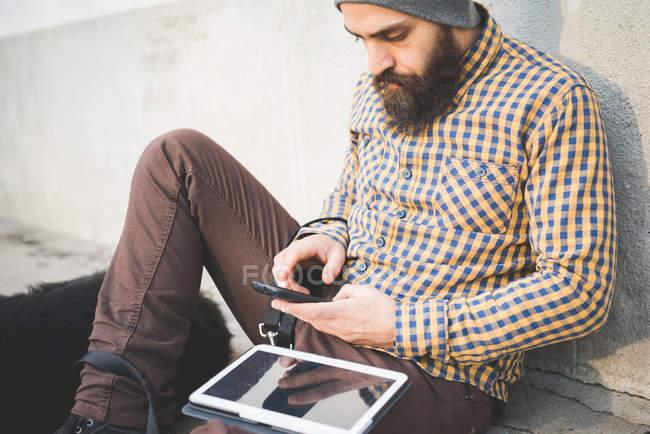 Взрослый мужчина сидит на улице с собакой, используя смартфон и цифровой планшет — стоковое фото