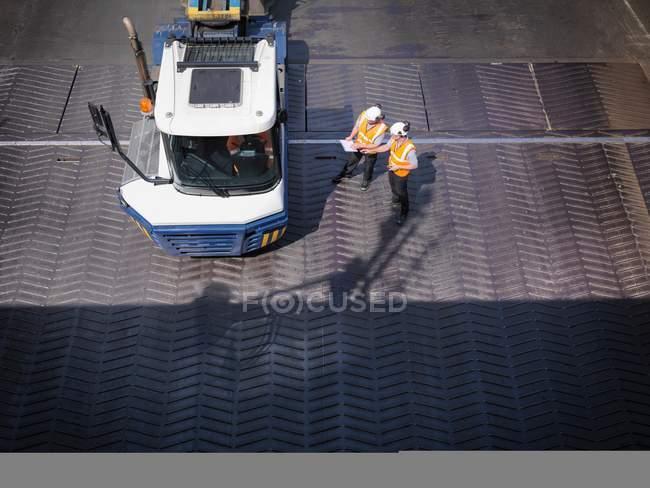 Рабочие в обсуждении с водителем грузовика на рампе судна, повышенный вид — стоковое фото