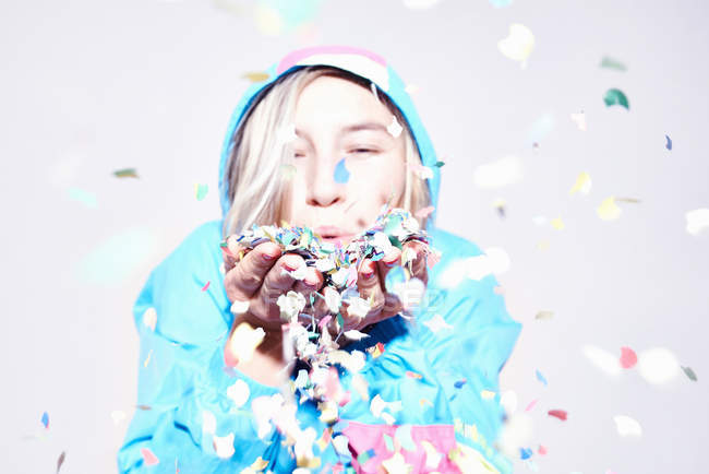 Portrait of young woman blowing confetti — Stock Photo