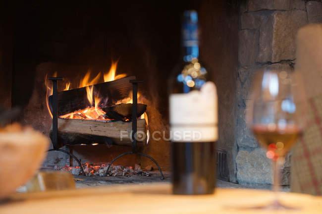 Бокал вина и бутылка камина — стоковое фото