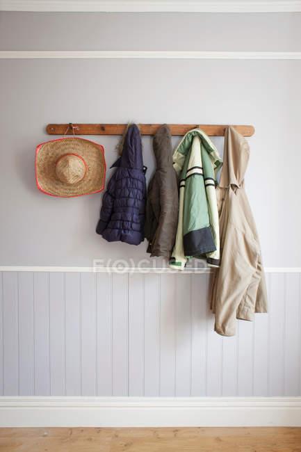Casacos e chapéu no rack do casaco — Fotografia de Stock