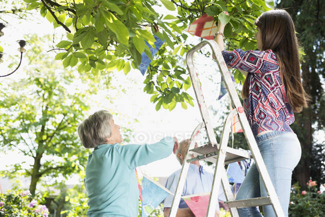 Grandparents and granddaughter hanging up bunting in garden — Stock Photo