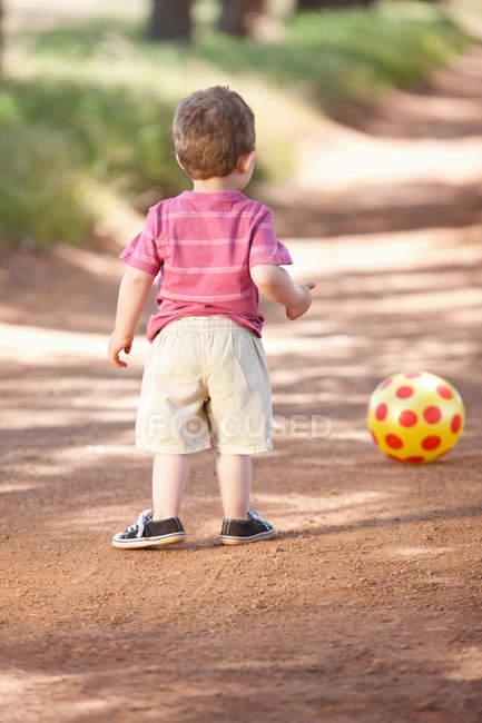 Niño pequeño con pelota en camino de tierra - foto de stock