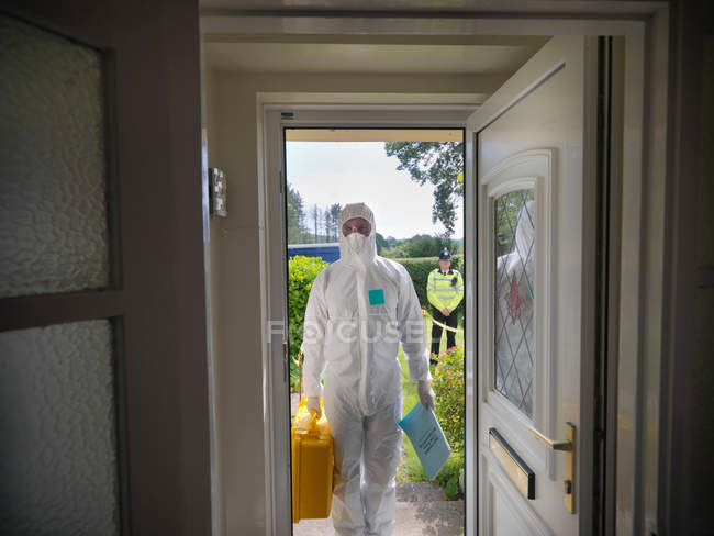 Forensic scientist entering house at crime scene, policeman in background — Stock Photo